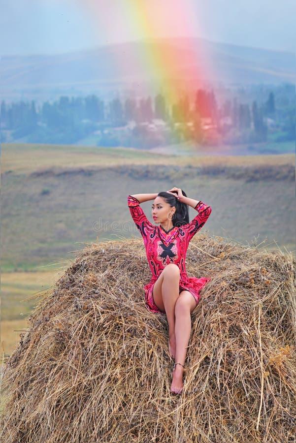 Ein Modell in einem hellen roten Kleid sitzt auf einem Heu lizenzfreie stockbilder
