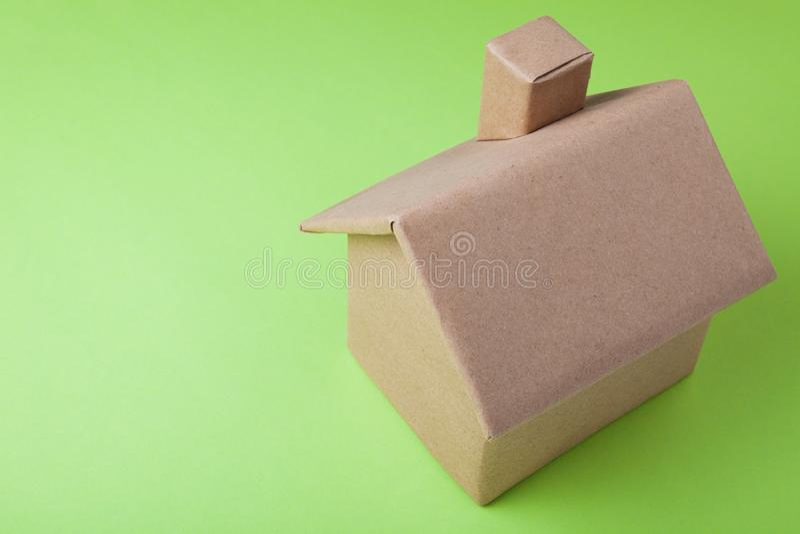 Ein Modell eines Papphauses auf einem grünen Hintergrund lizenzfreie stockfotografie