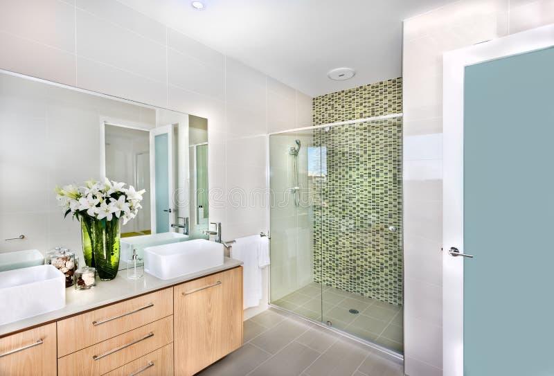 Ein modernes Badezimmer mit weißen Blumen im Vase stockfotos