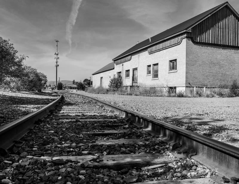 Ein modernes Schwarzweiss-Foto stellt verlassene Schienen und ein Depot dar stockfotografie