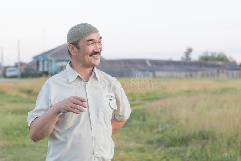 Ein moslemischer älterer Mann ist, sprechend stehend und über etwas Spaß stockbild