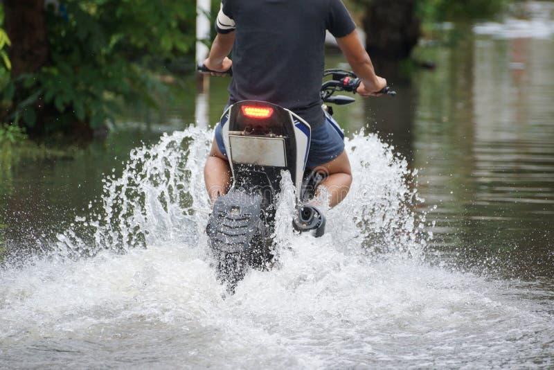 Ein Motorrad, das durch eine überflutete Straße fährt lizenzfreie stockfotos