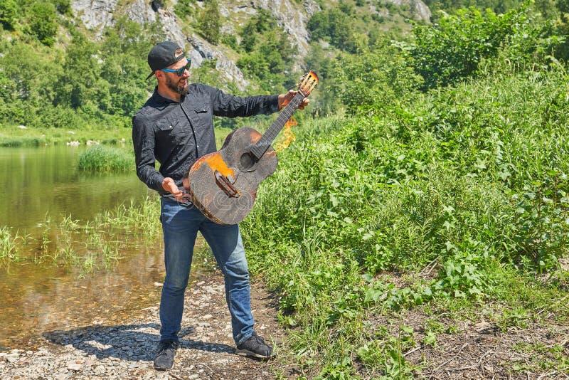 Ein Musiker spielt eine brennende Akustikgitarre gegen den Hintergrund von einer Naturlandschaft lizenzfreies stockbild
