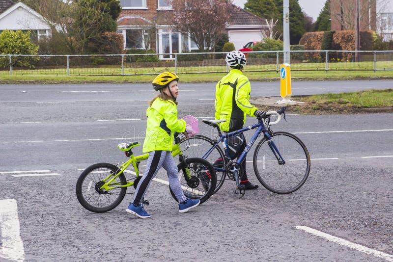 Ein Mutter- und Tochterweg mit ihren Zyklen über einer beschäftigten Straßenkreuzung stockfotografie