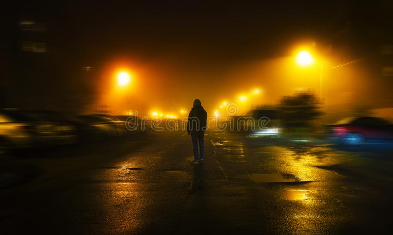 Ein mysteriöser Mann steht allein in der Straße, unter Autos in einer leeren Stadt, Wege die Nachtstraße, Träume lizenzfreie stockfotos
