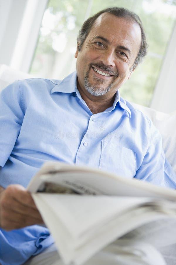 Ein nahöstlicher Mann, der zu Hause eine Zeitung liest lizenzfreie stockfotos