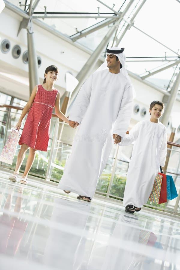 Ein nahöstlicher Mann mit dem Einkauf mit zwei Kindern stockbild