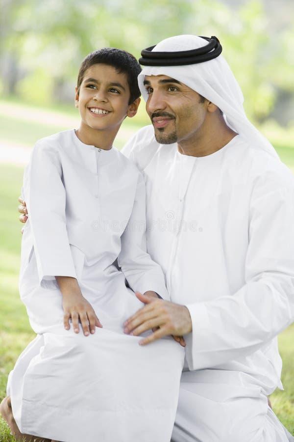 Ein nahöstlicher Mann und sein Sohn, die in einem Park sitzen stockfoto