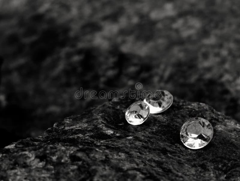 Ein Nahaufnahme-Bild, das von den zerstreuten Diamanten zeigen die Facetten des Edelsteins auf einem Felsen ist stockbild