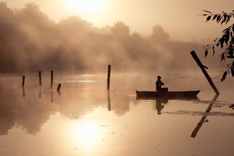 Ein nebelhafter Morgen durch den See Kleines Fischerboot am See lizenzfreies stockfoto