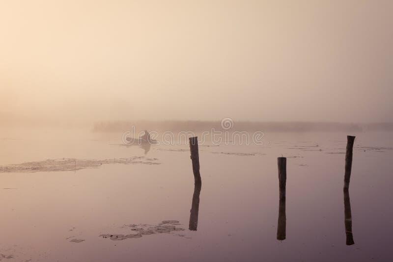 Ein nebelhafter Morgen durch den See Kleines Fischerboot am See lizenzfreie stockbilder