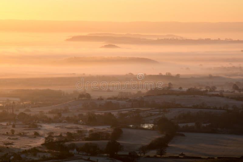 Ein nebeliger, eisiger Wintersonnenaufgang Mit Schichten Nebel über der englischen Landschaft worcestershire Großbritannien stockbilder