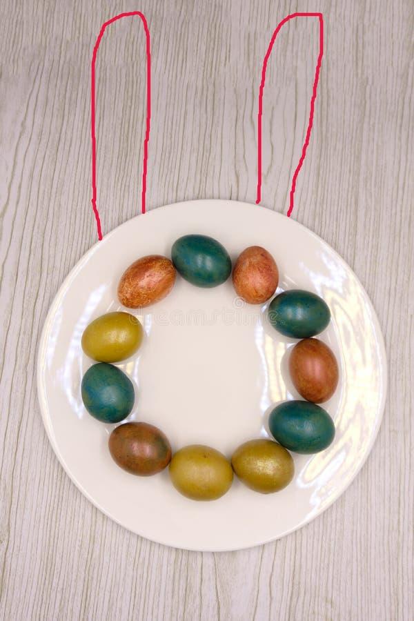 Ein Nest mit drei färbte Ostereier und Häschenohren zu Hause an Ostern-Tag Feiern von Ostern am Frühling Malereieier stockfotografie