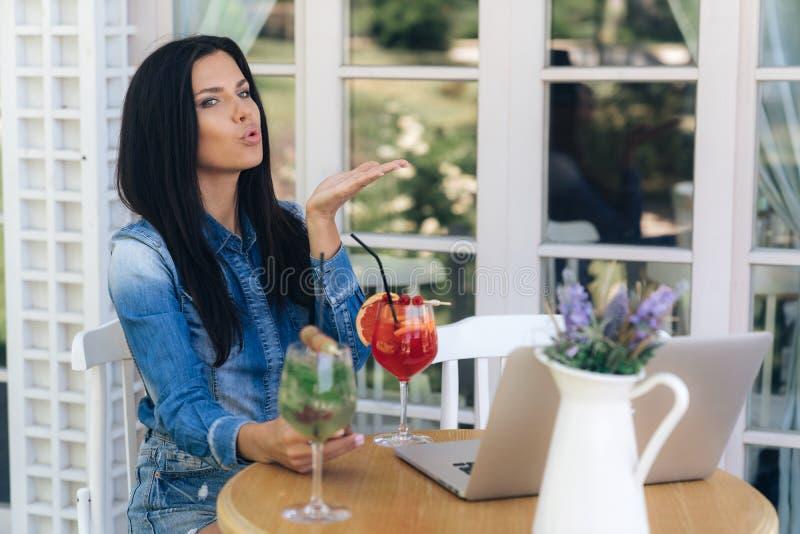 Ein netter netter Brunette, der an einem Tisch in einem Café, unter Verwendung der modernen Technologie und der Geräte sitzt, sch stockfotos