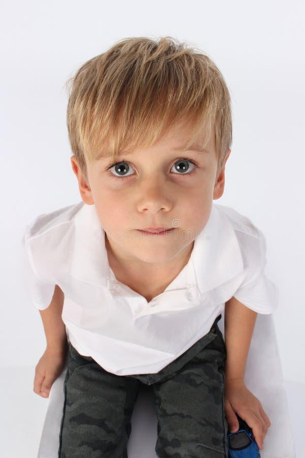 Ein netter hübscher jugendlicher Junge, der unschuldig sitzt und herzlichst und schaut lizenzfreie stockbilder