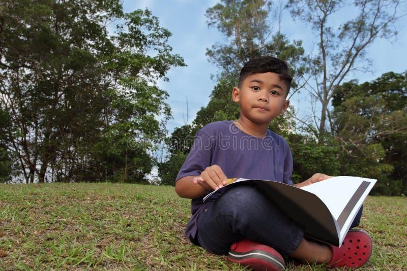 Ein netter Junge, der ein Buch in einem Park anstarrt entlang der Kamera liest stockfoto