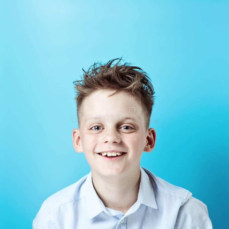 Ein netter Junge steht und lächelt in einem hellen Hemd auf einem hellen farbigen Hintergrund stockfotos