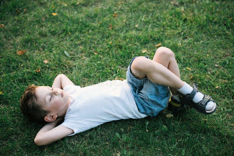 Ein netter kleiner Junge, der auf dem grünen Gras unter gefallenen Blättern im Park liegt lizenzfreie stockfotografie