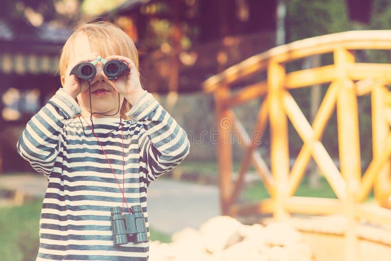 Ein netter kleiner Junge, der durch die Ferngläser im Freien schaut lizenzfreie stockfotos