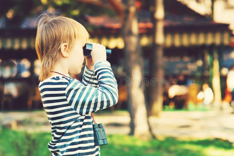 Ein netter kleiner Junge, der durch die Ferngläser im Freien schaut lizenzfreies stockfoto