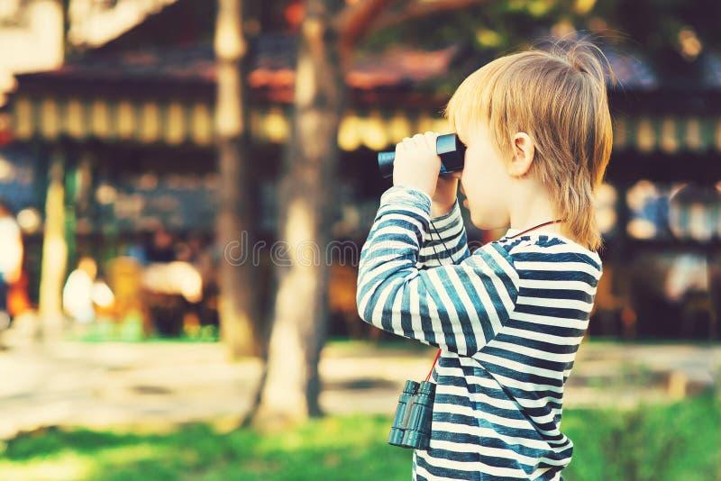 Ein netter kleiner Junge, der durch die Ferngläser im Freien schaut lizenzfreie stockbilder