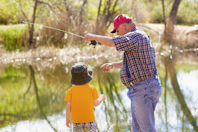 Little Boy und sein Großvater, die zusammen fischen stockfotografie