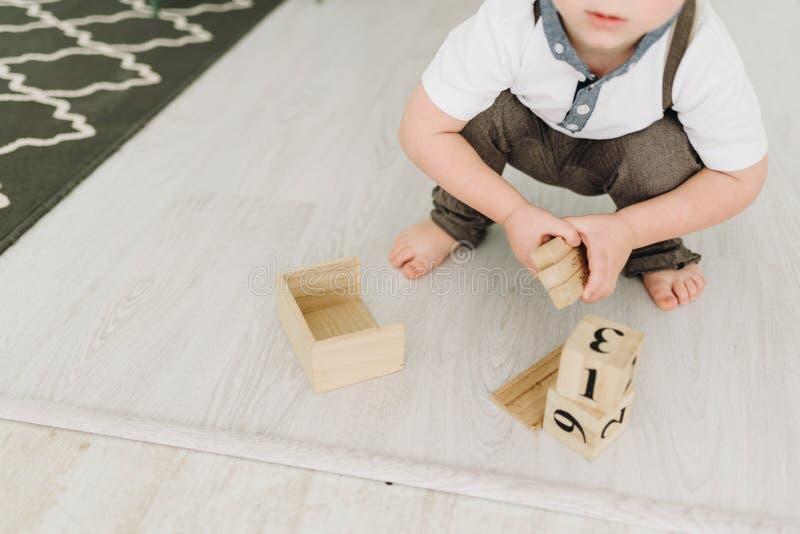 Ein netter kleiner Junge, der mit hölzernen Ziegelsteinen auf weißem Boden spielt lizenzfreie stockbilder