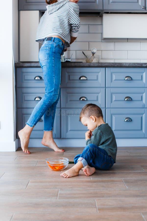 Ein netter kleiner Junge sitzt auf dem Küchenboden mit seiner Mutter im Hintergrund lizenzfreies stockbild