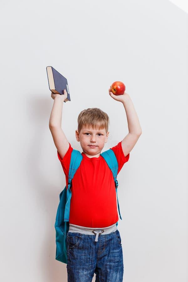 Ein netter Schüler mit Büchern und Äpfeln auf einem weißen Hintergrund stockfoto