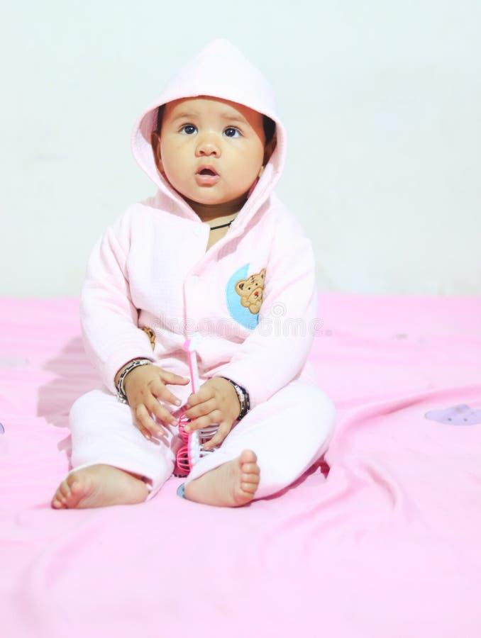 Ein nettes Baby, das nettes Gesicht den offenen Mund trägt das rosa Kleid, sitzend auf Bett macht stockbild