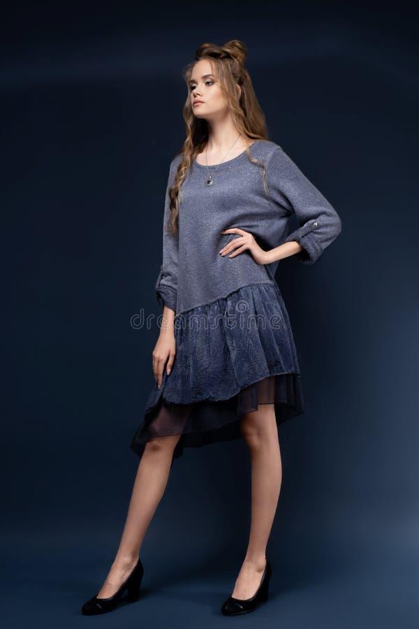 Ein nettes junges Mädchen in einem blauen Strickkleid auf einem blauen Hintergrund mit einem Haarschnitt und einem gelockten lang stockfotografie