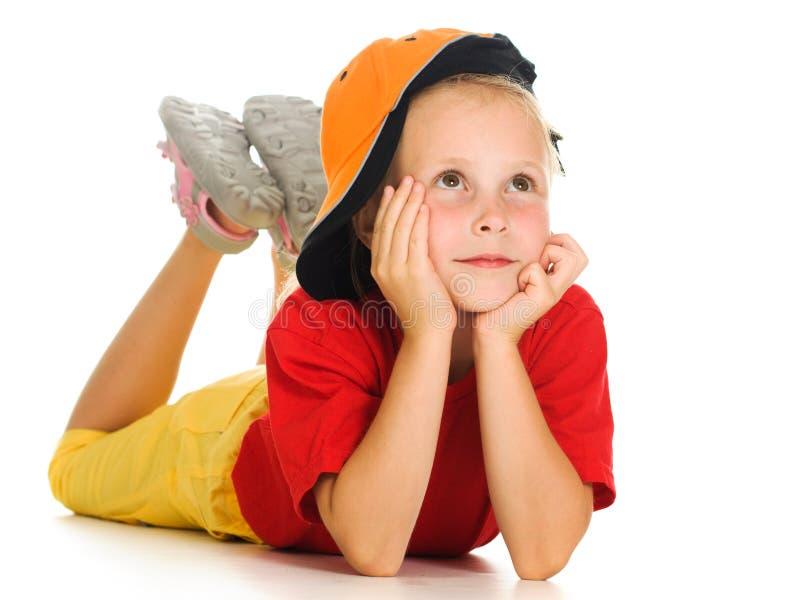 Ein nettes kleines Kind mit lustiger Schutzkappe liegt lizenzfreies stockfoto
