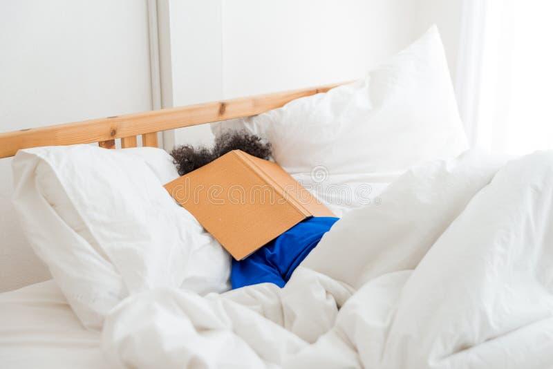Ein nettes kleines Kindafroamerikanermädchen schlafend und faul, wenn das Buch gelesen wird lizenzfreie stockfotografie
