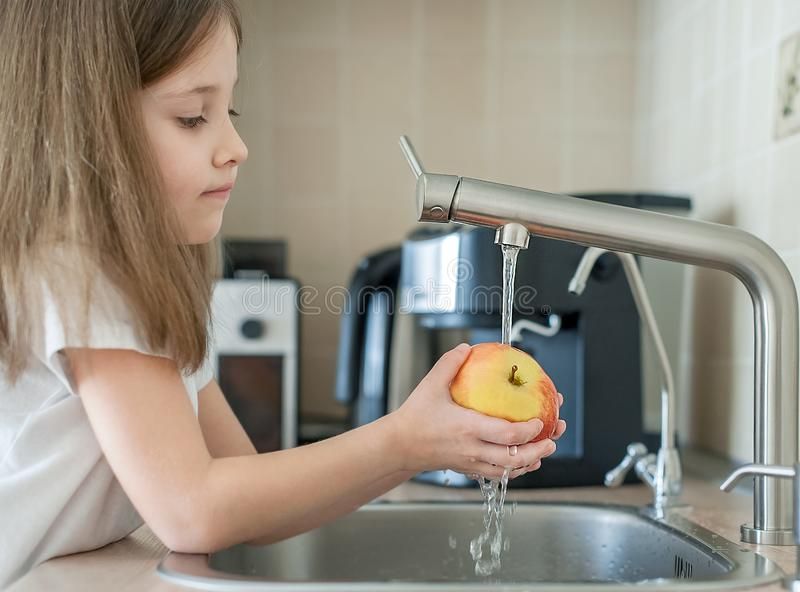 Ein nettes kleines M?dchen w?scht einen roten gelben Apfel in einer Wanne Kind w?scht die Frucht in der K?che Gesundes Lebensstil lizenzfreie stockbilder
