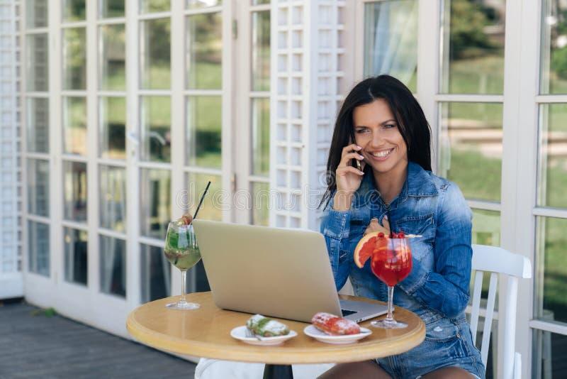 Ein nettes lächelndes junges Mädchen wird in den stilvollen zufälligen Jeans gekleidet Unterhaltung mit jemand am Telefon, sitzen lizenzfreie stockfotos