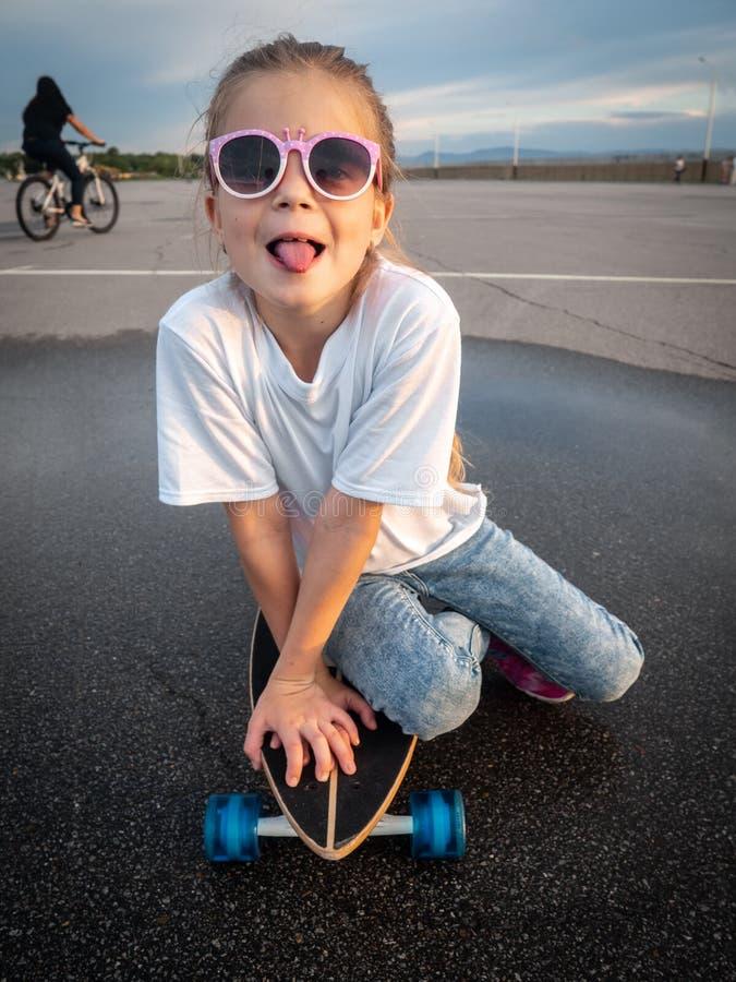 Ein nettes Mädchen in der Sonnenbrille sitzt auf einem longboard und zeigt ihre Zunge stockfoto