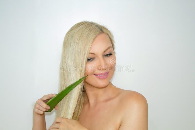 Ein nettes Mädchen hält Aloe Vera in ihren Händen und gibt ihr Haar Haarkosmetik lizenzfreies stockbild