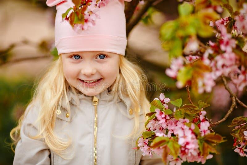 Ein nettes reizend blondes Mädchen mit dem üppigen Haar auf einer rosa Kirschblüte stockfotografie
