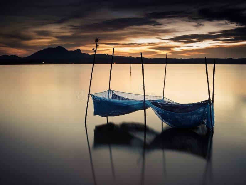 Ein Netz auf dem ruhigen Wasser im Sonnenuntergang stockbilder