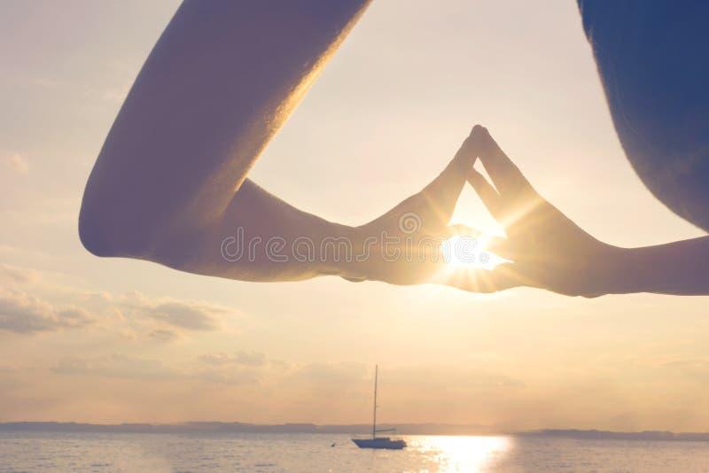 Ein neuer Morgen fängt mit dem Sonnenaufgang an, der in den Händen einer meditierenden Frau geschützt wird stockfotografie