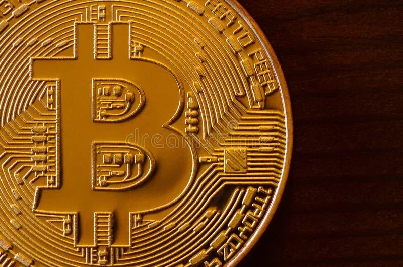 Ein neues goldenes körperliches bitcoin ist Lügen auf dunklem hölzernem backgound, Abschluss oben Hohes Auflösung-Foto Cryptocurr stockfoto