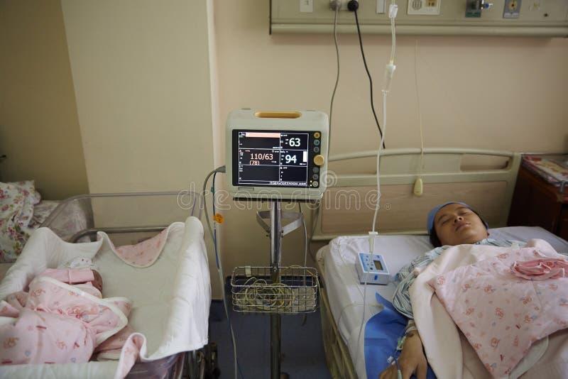 Ein neugeborenes und eine Mutter unter Überwachung durch Maschine stockbild