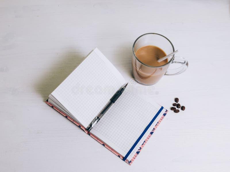 Ein Notizbuch auf dem Tisch nahe bei Glas Kaffee stockfotografie