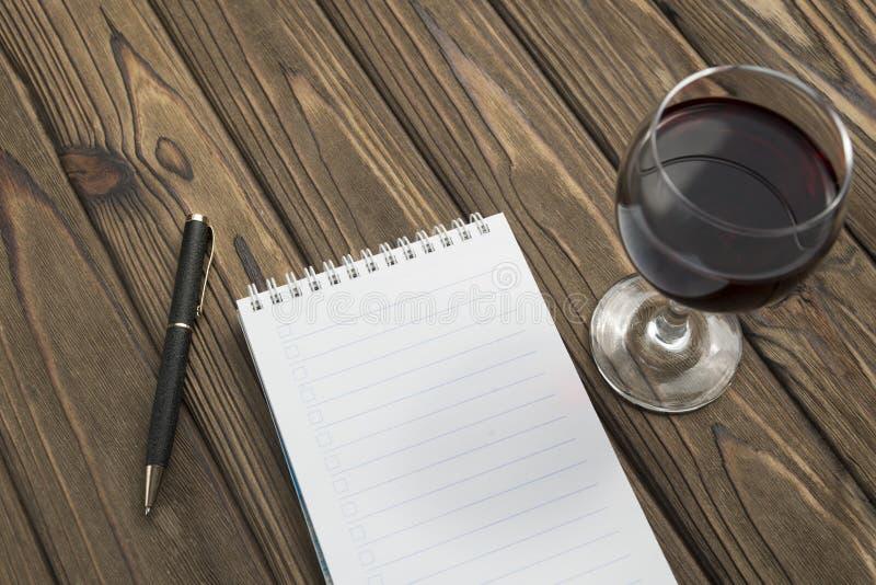 Ein Notizbuch auf einer Spirale, ein Kugelschreiber, ein Glas Rotwein auf einem Holztischhintergrund lizenzfreies stockbild