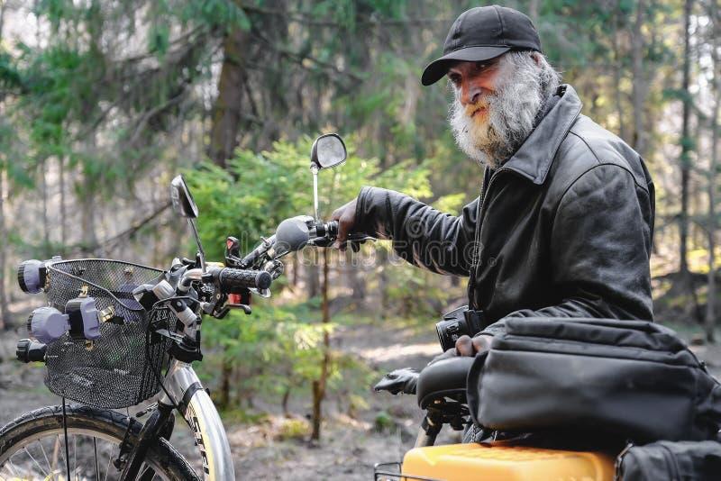 Ein obdachloser Mann in den Fahrten eines Rollstuhls auf einen Waldweg Der dreirädrige Rollstuhl wird mit einem Kasten für Sachen lizenzfreie stockbilder