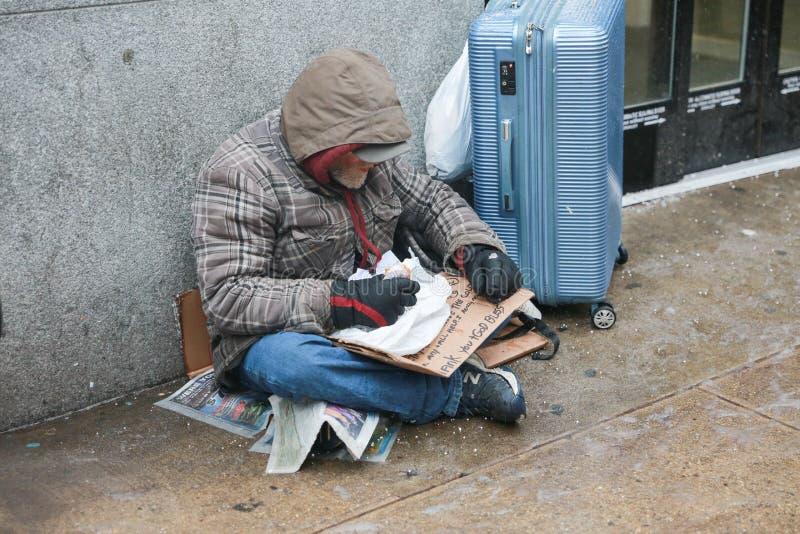 Ein obdachloser Mann isst Nahrung in Manhattan-Straße stockfotos