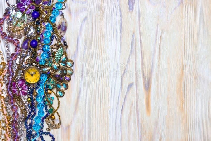Ein obenliegendes Foto von netten lila natürlichen Amethystperlen, -steinen, -kristallen und -halsketten auf dem Holztisch Mehrfa lizenzfreie stockfotos