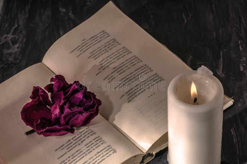 Ein offenes Buch mit einer Kerze auf den Seiten ist eine Knospe der getrockneten Rose lizenzfreies stockbild