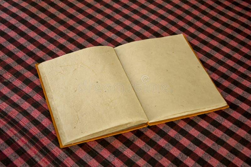 Ein offenes orange Buch mit Leerbelegen des natürlichen rauen Papiers liegt auf der karierten Tischdecke der Tabelle weiße rote s stockfotografie
