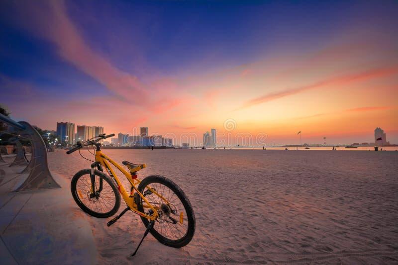 Ein orange Farbfahrrad parkt im corniche Strand Abu Dhabi lizenzfreies stockfoto